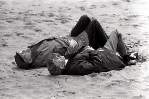 August Bank Holiday in Blackpool, 1971. Two elderly men in flat caps and coats asleep on the beach sunbathing Don McPhee : Photographer Exhibition at the Newsroom